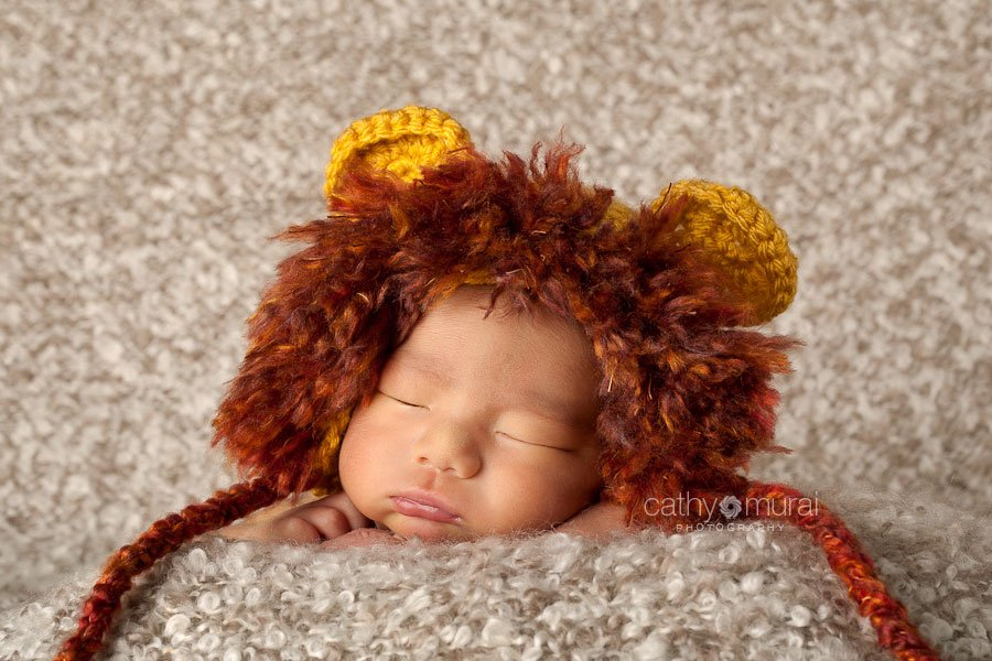 Newborn with a lion hat posing