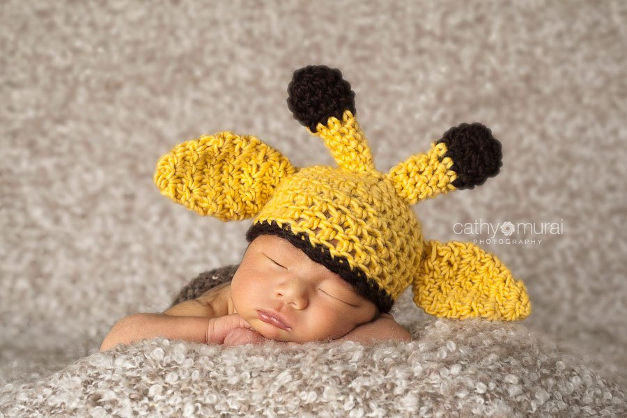 Sleeping newborn with a giraffe hat posing