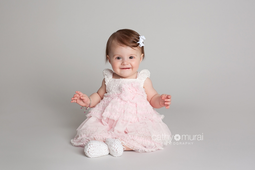 7months old baby in beautiful light pink dress smiling and sitting up by herself during baby portrait session taken by Alhambra Baby Photographer, Cathy Murai Photography
