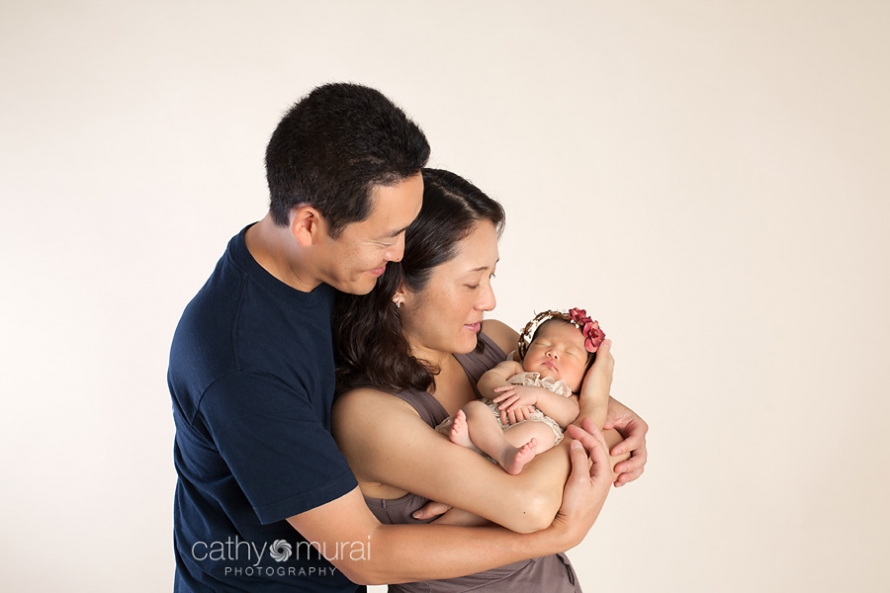 A family portrait of Asian parents and a beautiful 8 day old newborn baby girl wearing the red halo and the cream lace romper.  A family portrait taken in the studio during newborn portrait session, Los Angeles, San Gabriel Valley, Alhambra Newborn Photographer, Cathy Murai Photography