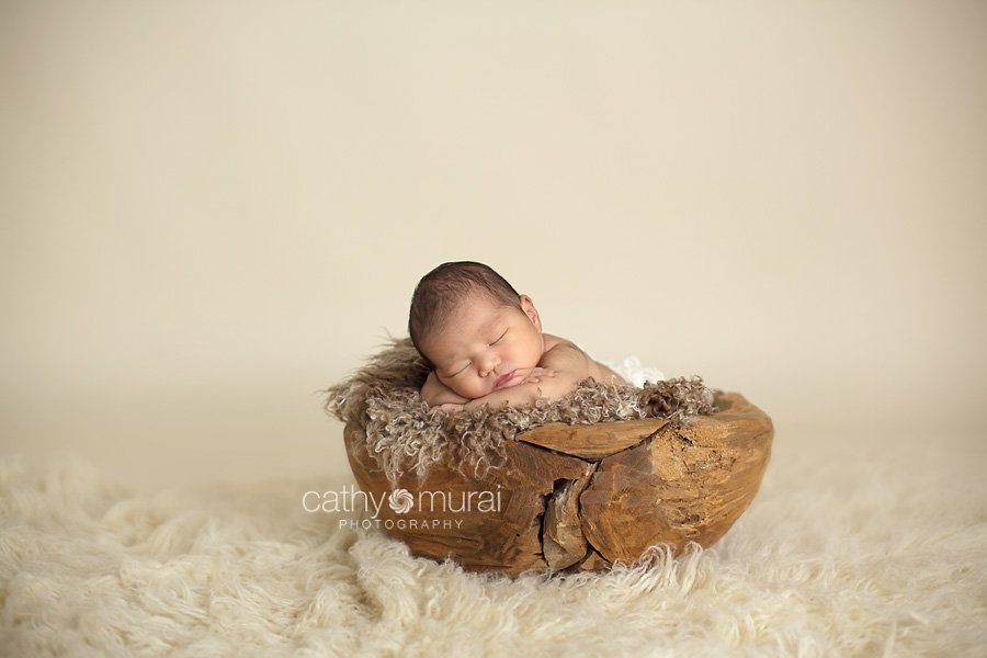 Asian 2 weeks newborn baby girl posing and sleeping on brown furry prop / blanket inside the wooden puzzled bowl on float rug in front of tan, ivory, cream background. Alhambra, San Gabriel Valley, Los Angeles, CA  Studio Newborn Photographer, Cathy Murai Photography