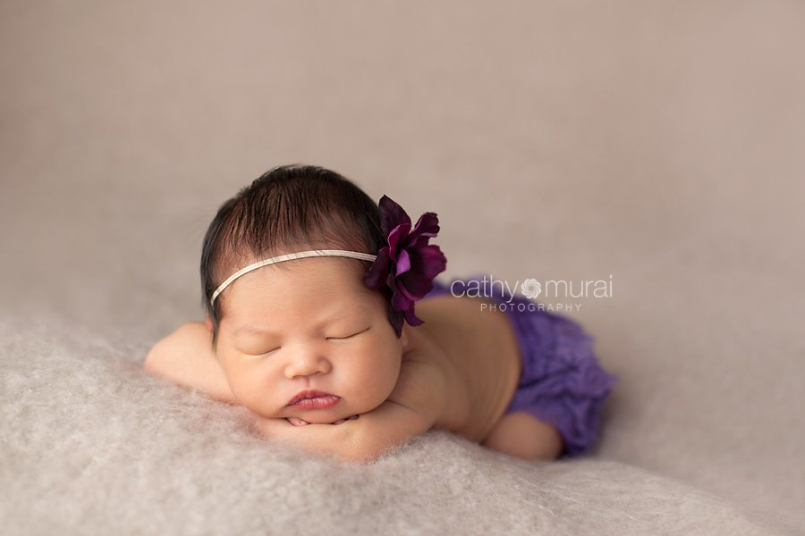 Newborn baby girl wearing a purple flower head band and lace diaper cover sleeping and posing