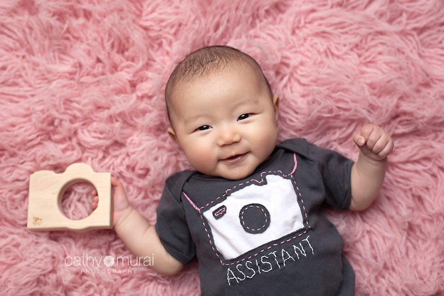 3 months old baby girl wearing a grey photographer assistant onesie from Amy Tagerine and holding a wooden camera teething toy from Little Spling Toys.  Los Angeles Newborn & Baby Photographer, Cathy Murai Photography is back from maternity leave