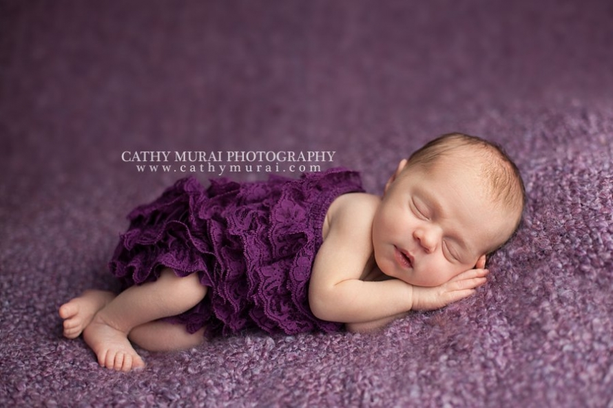 Precious Newborn Baby Girl, wearing a purple lace romper, posing on the bean bag beanbag with purple throw cover, Los Angeles. Pasadena, Newborn photographer, Cathy Miurai Photography