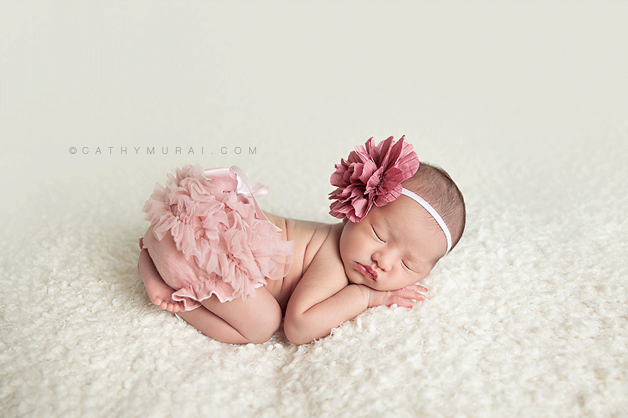 Newborn baby girl wearing pink diaper cover and pink headband sleeping and posing on white background