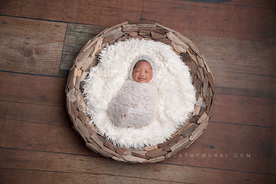 preemie newborn baby photography, preemie newborn baby picture, preemie newborn baby image, preemie newborn baby portrait, preemie newborn baby at 5 weeks old, wearing white knit hat and wrap, smiling while sleeping on wooden puzzled basket on the wood floor, captured by los angeles newborn baby photographer, los angeles  preemie photographer, los angeles newborn photographer, alhambar newborn baby photographer, lalhambra  preemie photographer, alhambra newborn photographer,  studio newborn photographer, Cathy Murai Photography