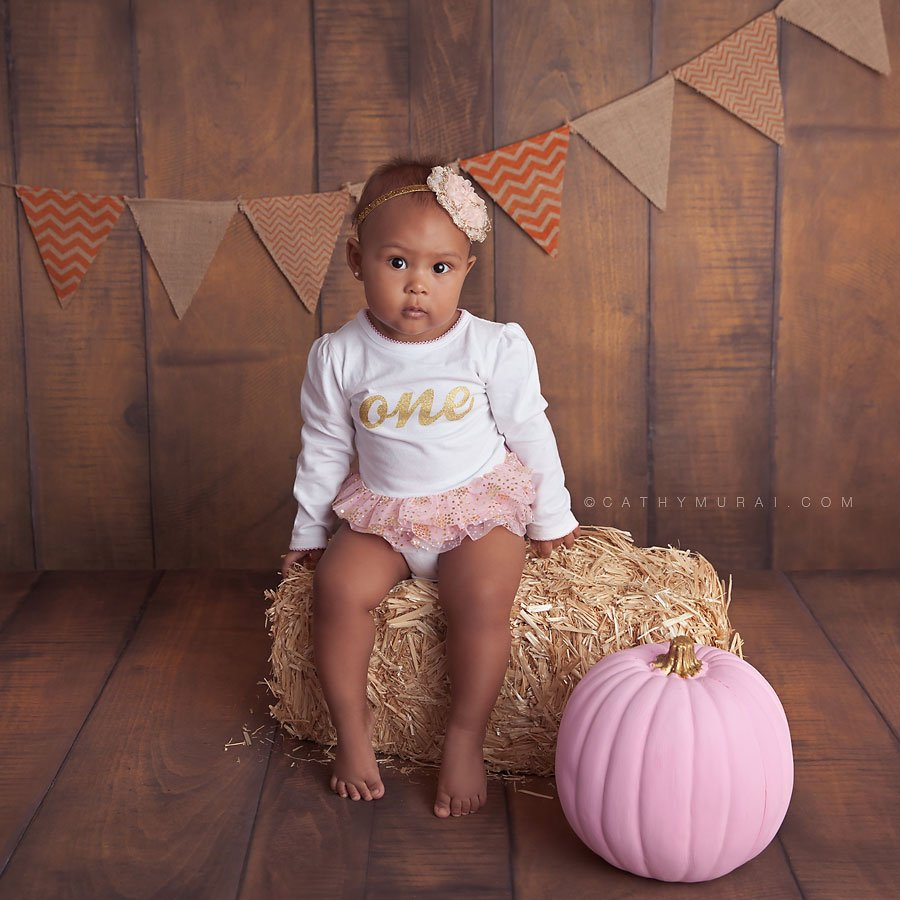 1st birthday girl wearing one onesie and sitting on a bale of hale with a pink pumpkin, pink pumpkin patch. LOS ANGELES Birthday Portraits, LOS ANGELES 1st Birthday Portraits, LOS ANGELES first Birthday pictures, LOS ANGELES Birthday Photographer, LOS ANGELES Birthday Photography, LOS ANGELES first Birthday Photography, LOS ANGELES first Birthday Photographer, LOS ANGELES 1st Birthday Photographer, , LOS ANGELES 1st Birthday Photography, LOS ANGELES Baby Photographer, LOS ANGELES Baby Photography, LOS ANGELES Family Photographer, LOS ANGELES Family Photography, Los Angeles Smash Cake, Los Angles Cake Smash, LA Birthday Portaits, LA 1st Birthday Portarits, LA first Birthday pictures, LA Birthday Photographer, LA Birthday Photography, LA first Birthday Photographer, LA first Birthday Photography, LA Baby Photographer, LA Baby Photography, LA Family Photographer, LA Family Photography, LA Smash Cake, LA Cake Smash, PASADENA Birthday Portraits, PASADENA 1st Birthday Portraits, PASADENA first Birthday pictures, PASADENA Birthday Photographer, PASADENA Birthday Photography, PASADENA first Birthday Photography, PASADENA first Birthday Photographer, PASADENA 1st Birthday Photographer, , PASADENA 1st Birthday Photography, PASADENA Baby Photographer, PASADENA Baby Photography, PASADENA Family Photographer, PASADENA Family Photography, Pasadena Smash Cake, Los Angles Cake Smash, SAN GABIEL VALLEY Birthday Portraits, SAN GABIEL VALLEY 1st Birthday Portraits, SAN GABIEL VALLEY first Birthday pictures, SAN GABIEL VALLEY Birthday Photographer, SAN GABIEL VALLEY Birthday Photography, SAN GABIEL VALLEY first Birthday Photography, SAN GABIEL VALLEY first Birthday Photographer, SAN GABIEL VALLEY 1st Birthday Photographer, , SAN GABIEL VALLEY 1st Birthday Photography, SAN GABIEL VALLEY Baby Photographer, SAN GABIEL VALLEY Baby Photography, SAN GABIEL VALLEY Family Photographer, SAN GABIEL VALLEY Family Photography, San Gabiel Valley Smash Cake, Los Angles Cake Smash, ALHAMBRA Birthday Portraits, ALHAMBRA 1st Birthday Portraits, ALHAMBRA first Birthday pictures, ALHAMBRA Birthday Photographer, ALHAMBRA Birthday Photography, ALHAMBRA first Birthday Photography, ALHAMBRA first Birthday Photographer, ALHAMBRA 1st Birthday Photographer, , ALHAMBRA 1st Birthday Photography, ALHAMBRA Baby Photographer, ALHAMBRA Baby Photography, ALHAMBRA Family Photographer, ALHAMBRA Family Photography, Alhambra Smash Cake, Los Angles Cake Smash, SAN MARINOBirthday Portraits, SAN MARINO1st Birthday Portraits, SAN MARINOfirst Birthday pictures, SAN MARINOBirthday Photographer, SAN MARINOBirthday Photography, SAN MARINOfirst Birthday Photography, SAN MARINOfirst Birthday Photographer, SAN MARINO1st Birthday Photographer, , SAN MARINO1st Birthday Photography, SAN MARINOBaby Photographer, SAN MARINOBaby Photography, SAN MARINOFamily Photographer, SAN MARINOFamily Photography, San MarinoSmash Cake, Los Angles Cake Smash, TEMPLE CITYBirthday Portraits, TEMPLE CITY1st Birthday Portraits, TEMPLE CITYfirst Birthday pictures, TEMPLE CITYBirthday Photographer, TEMPLE CITYBirthday Photography, TEMPLE CITYfirst Birthday Photography, TEMPLE CITYfirst Birthday Photographer, TEMPLE CITY1st Birthday Photographer, , TEMPLE CITY1st Birthday Photography, TEMPLE CITYBaby Photographer, TEMPLE CITYBaby Photography, TEMPLE CITYFamily Photographer, TEMPLE CITYFamily Photography, Temple CitySmash Cake, Los Angles Cake Smash, ROSEMEADBirthday Portraits, ROSEMEAD1st Birthday Portraits, ROSEMEADfirst Birthday pictures, ROSEMEADBirthday Photographer, ROSEMEADBirthday Photography, ROSEMEADfirst Birthday Photography, ROSEMEADfirst Birthday Photographer, ROSEMEAD1st Birthday Photographer, , ROSEMEAD1st Birthday Photography, ROSEMEADBaby Photographer, ROSEMEADBaby Photography, ROSEMEADFamily Photographer, ROSEMEADFamily Photography, RosemeadSmash Cake, Los Angles Cake Smash, DOWNTOWN LOS ANGELES Birthday Portraits, DOWNTOWN LOS ANGELES 1st Birthday Portraits, DOWNTOWN LOS ANGELES first Birthday pictures, DOWNTOWN LOS ANGELES Birthday Photographer, DOWNTOWN LOS ANGELES Birthday Photography, DOWNTOWN LOS ANGELES first Birthday Photography, DOWNTOWN LOS ANGELES first Birthday Photographer, DOWNTOWN LOS ANGELES 1st Birthday Photographer, , DOWNTOWN LOS ANGELES 1st Birthday Photography, DOWNTOWN LOS ANGELES Baby Photographer, DOWNTOWN LOS ANGELES Baby Photography, DOWNTOWN LOS ANGELES Family Photographer, DOWNTOWN LOS ANGELES Family Photography, Downtown Los Angeles Smash Cake, Los Angles Cake Smash