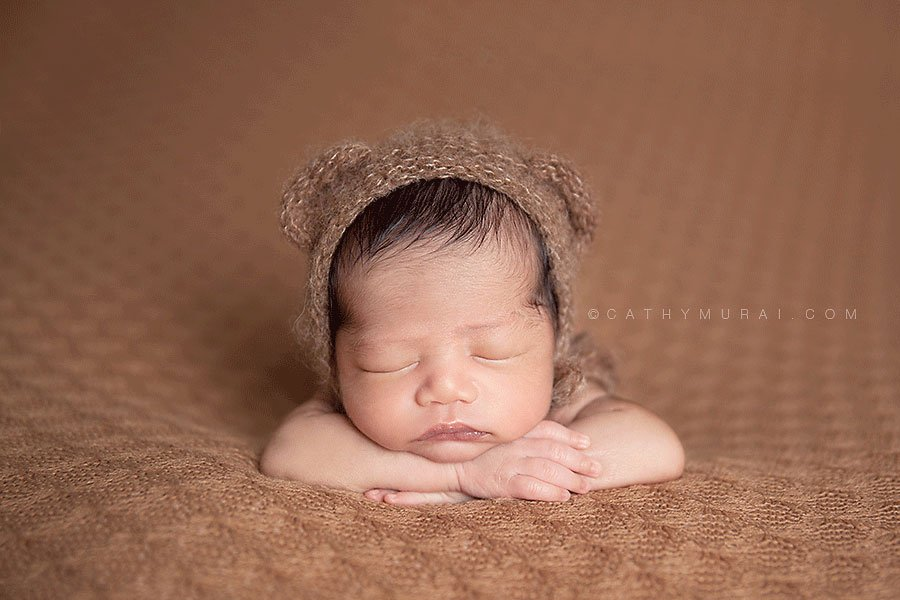 Newborn baby boy wearing a teddy bear hat sleeping on his both arms los