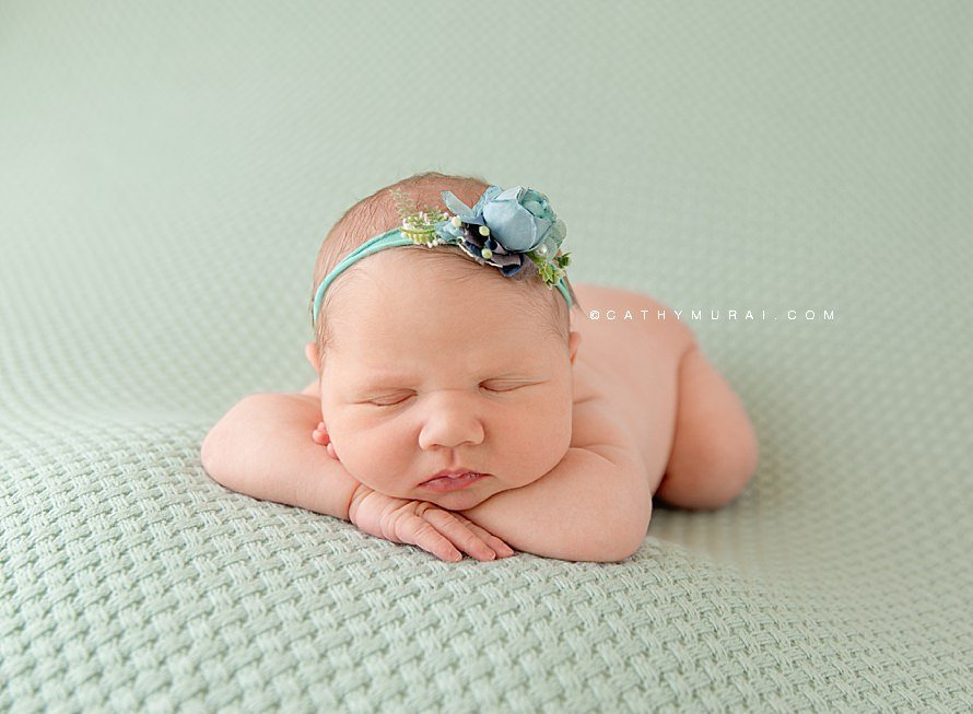 Cathy Murai Photography is a Irvine Newborn photographer based in Orange County, CA.   This adorable newborn picture was captured in her Irvine Newborn Photography studio, Newborn baby girl wearing a teal and blue headband posing Hand on chin pose and Chin on wrists pose while she was sleeping on the teal blue backdrop blanket during her newborn session in Irvine, CA.