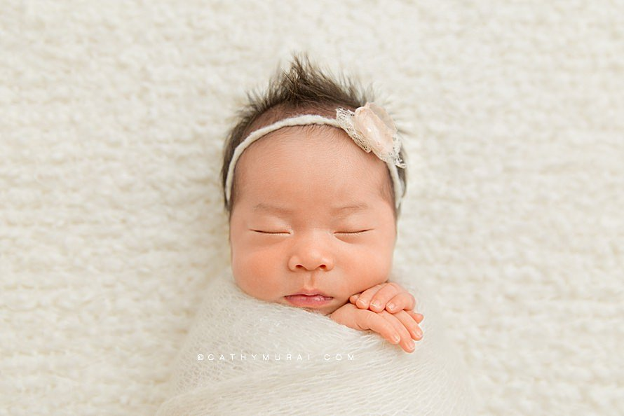 Natural Organic Newborn Photography Session by Cathy Murai Photography, Orange County Newborn and baby photographer in Irvine, a newborn baby girl wearing a cream headband is in simple wrapped pose, closeup newborn image.jpg
