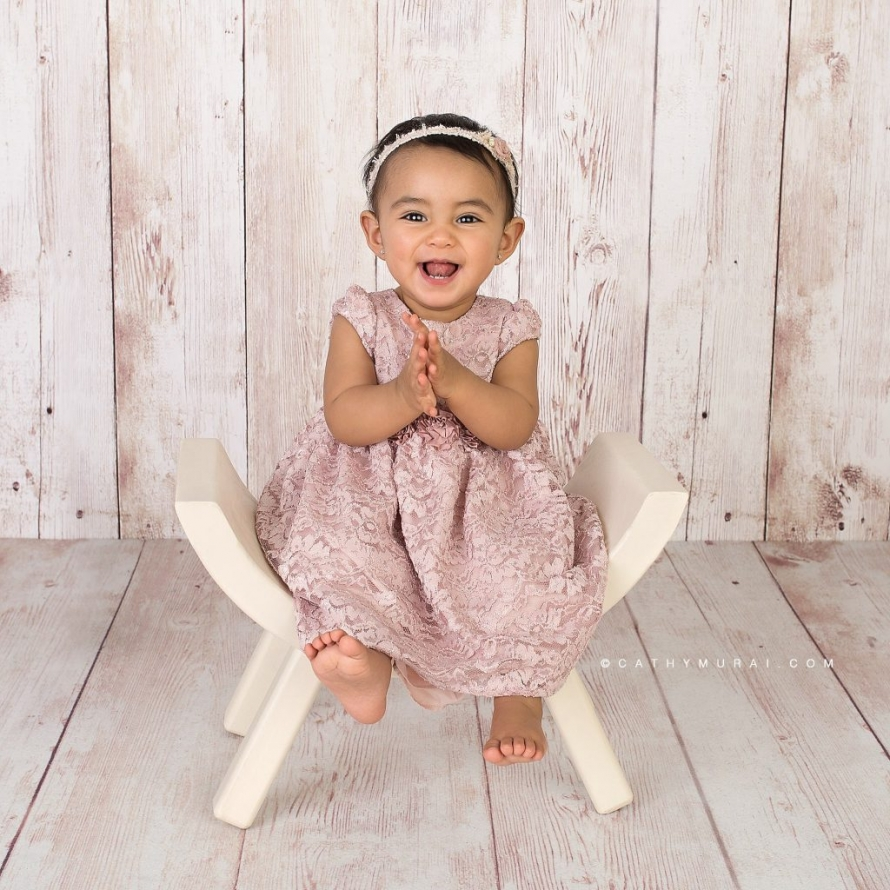 Happy first birthday girl on a cream curved wooden chair during her first birthday photoshoot by Cathy Murai Photography, a Irvine baby photographer