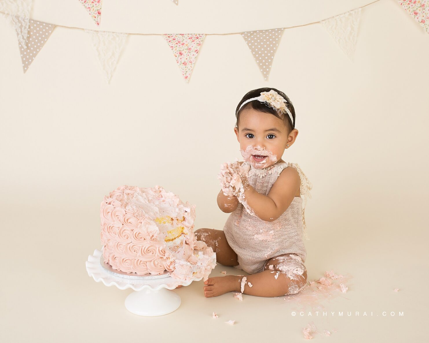 Getting messy during First Birthday Cake Smash Photography session with a vintage style using a pink cake, white cake stand, and a vintage banner, captured by Cathy Murai Photography, a Irvine baby photographer