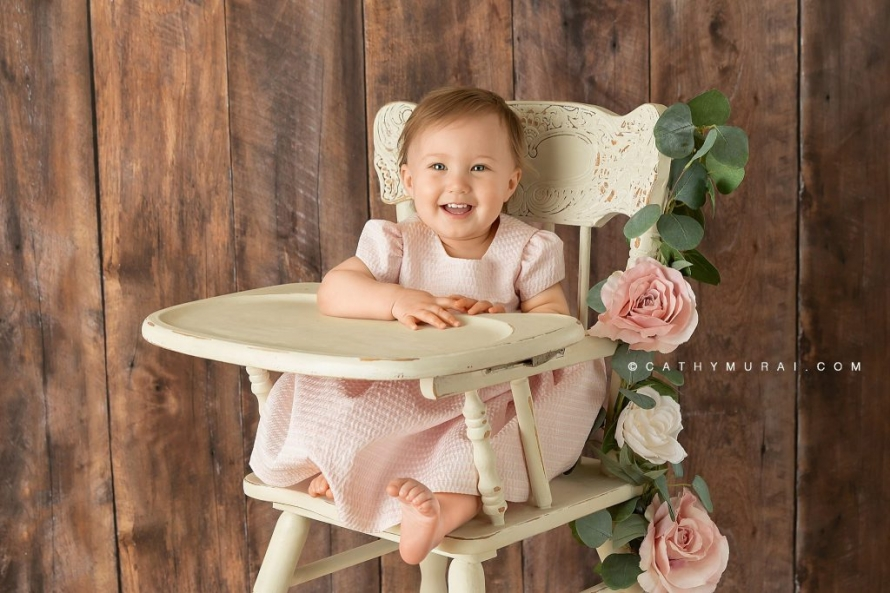 happy first birthday girl on a white vintage high chair / cream vintage high chair decorated with pink flowers during her first birthday photoshoot with Cathy Murai Photography, a Irvine baby photographer