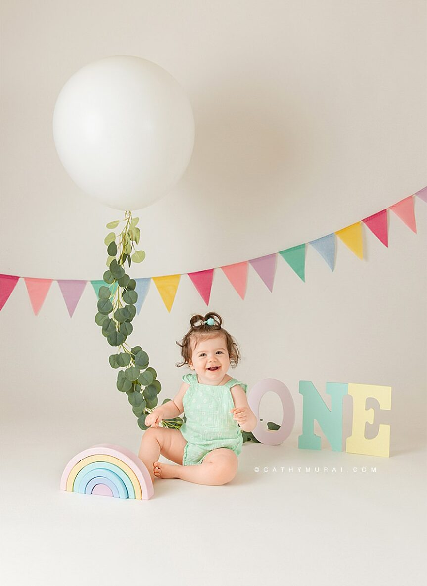 Pastel rainbow themed first birthday photo session using props including a rainbow wooden toy, o.n.e. letters in the pastel color, pastel banner, and a pastel outfit for the first birthday girl